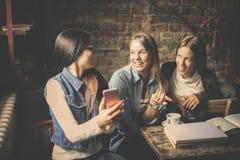 Trois filles d'étudiants ayant la conversation et à l'aide du téléphone intelligent Image stock