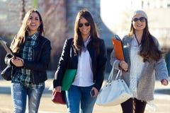 Trois filles d'étudiants marchant dans le campus de l'université Image stock