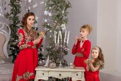 Trois filles dans une robe de soirée rouge l'arbre de Noël Image libre de droits