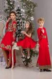 Trois filles dans une robe de soirée rouge l'arbre de Noël Image stock