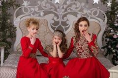 Trois filles dans une robe de soirée rouge l'arbre de Noël Images stock