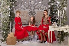 Trois filles dans une robe de soirée rouge l'arbre de Noël Photographie stock libre de droits