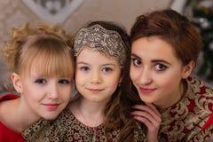 Trois filles dans une robe de soirée rouge l'arbre de Noël Images libres de droits