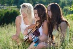 Trois filles de l'adolescence heureuses chantant et jouant la guitare sur l'herbe verte Images stock