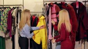 Trois filles de mode regardant un manteau de fourrure jaune-brun un magasin d'habillement clips vidéos