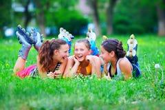 Trois filles de rouleau ayant l'amusement sur le champ vert Images stock