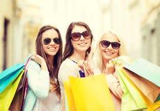 Trois filles de sourire avec des paniers dans la ville Images stock
