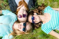 Trois filles de sourire heureuses se trouvant sur l'herbe verte dans des lunettes de soleil Photos libres de droits