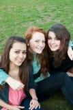 Trois filles différentes s'asseyent sur l'herbe et Photo stock