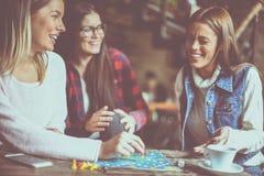 Trois filles gaies jouant le jeu de société Photo stock