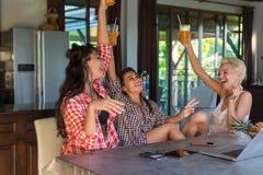 Trois filles gaies s'asseyant au Tableau dans des mains augmentées de sourire heureuses de cuisine tenant le jus d'orange, positi Photo stock