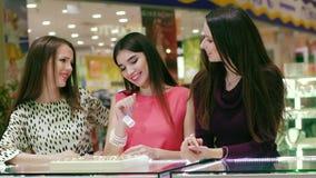 Trois filles heureuses choisissant un anneau à l'un d'entre eux banque de vidéos