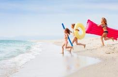 Trois filles heureuses courant ensemble en mer tropicale Photos stock