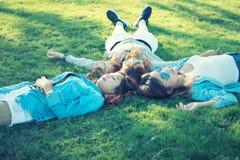 Trois filles heureuses de l'Asie se trouvant sur l'herbe verte dans des lunettes de soleil photo libre de droits