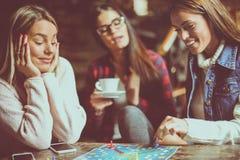 Trois filles heureuses jouant le jeu de société Image stock