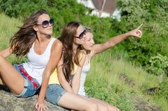 Trois filles heureuses révélant se reposer sur la pelouse verte Images stock