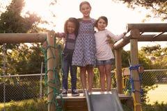 Trois filles jouant dehors à la maison sur la glissière de jardin Photo libre de droits