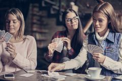 Trois filles jouant la carte en café Photographie stock libre de droits