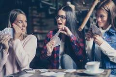 Trois filles jouant la carte en café Image stock