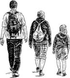 Trois filles marchant loin sur une promenade Images stock
