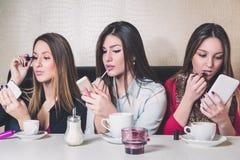 Trois filles mettant sur le maquillage dans un café Photos stock