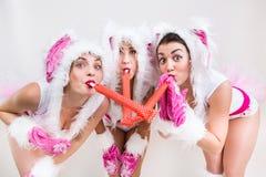 Trois filles mignonnes dans un lapin blanc et le costume rose soufflant dans le tuyau photos stock