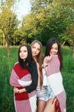 Trois filles mignonnes se tenant dans le plaid dehors, des meilleurs amis ayant l'amusement et riant dans le parc Images libres de droits