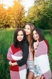 Trois filles mignonnes se tenant dans le plaid dehors, des meilleurs amis ayant l'amusement et riant dans le parc Photographie stock