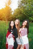 Trois filles mignonnes se tenant dans le plaid dehors, des meilleurs amis ayant l'amusement et riant dans le parc Photos stock