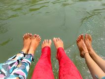 Trois filles montrant des jambes dans rivière Photographie stock libre de droits