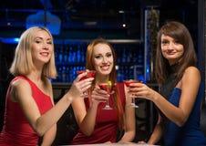 Trois filles ont soulevé leurs verres dans une boîte de nuit Photographie stock