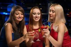 Trois filles ont soulevé leurs verres dans une boîte de nuit Images stock