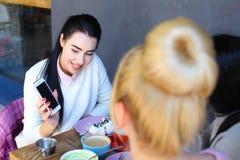 Trois filles parlant et s'asseyent en café Fille assez jeune avec le blac Images stock