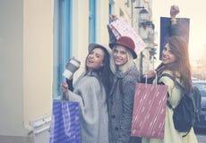Trois filles posant sur la rue après l'achat regarder est venu Image libre de droits