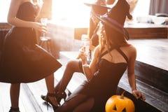 Trois filles reposent et font tinter des verres avec le champagne Photographie stock