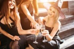 Trois filles reposent et font tinter des verres avec le champagne Images libres de droits