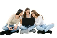 Trois filles s'asseyant au sol, les jambes croisées, tenant l'ordinateur portable image libre de droits