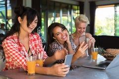Trois filles s'asseyant au sourire heureux de téléphones intelligents de cellules d'utilisation de Tableau, jeune femme causant l Images stock