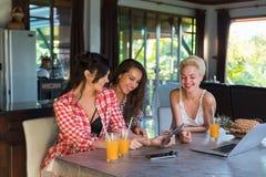 Trois filles s'asseyant au sourire heureux de tablette d'utilisation de Tableau, amies de jeune femme ensemble Photographie stock libre de droits