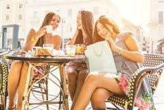 Trois filles s'asseyant dans une barre et célébrant l'anniversaire Photo stock