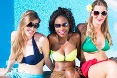 Trois filles s'asseyant sur la piscine dans la détente d'été Photographie stock libre de droits