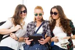 Trois filles se tiennent à l'aéroport et à regarder le comprimé Un voyage avec des amis Images libres de droits