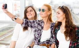 Trois filles se tiennent à l'aéroport et à regarder le comprimé Un voyage avec des amis Filles faisant le selfie Images libres de droits