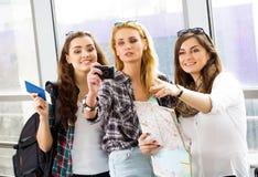 Trois filles se tiennent à l'aéroport et à regarder le comprimé Un voyage avec des amis Filles faisant le selfie Photographie stock libre de droits