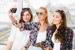 Trois filles se tiennent à l'aéroport et à regarder le comprimé Un voyage avec des amis Filles faisant le selfie Photo stock