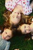Trois filles se trouvant sur l'herbe Image libre de droits