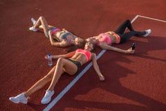 Trois filles se trouvant sur le plancher détendant après la formation Photos libres de droits