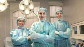 Trois filles soignent dans la salle d'opération enlèvent le masque protecteur et sourient clips vidéos