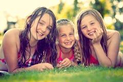 Trois filles souriant sur un pré Photos libres de droits