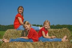 Trois filles sur des balles de paille. Photo stock